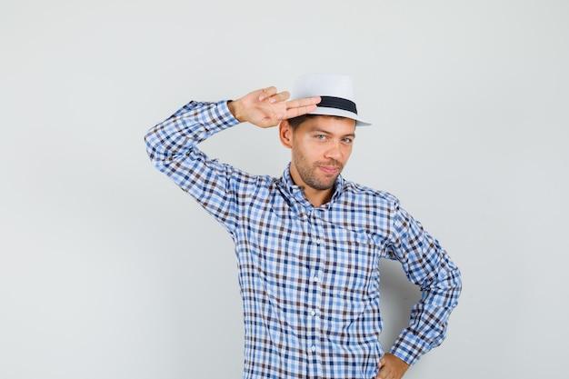 手と指で身振りで示す若い男は、チェックのシャツを着て、自信を持って頭に向かっています。