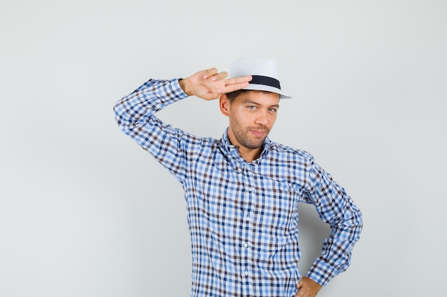 Young man gesturing with hand and fingers to head in checked shirt and looking confident.