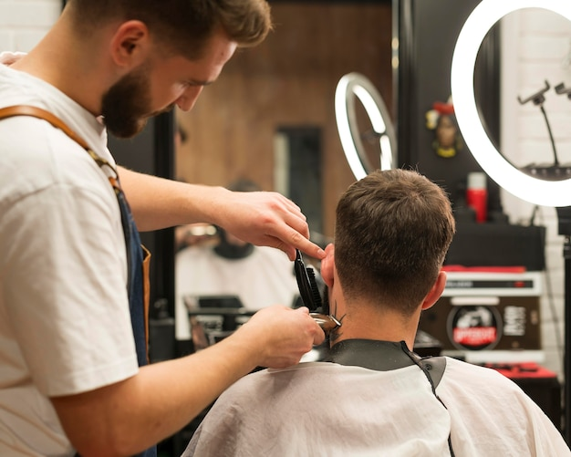 Молодой человек делает новую стрижку в парикмахерской