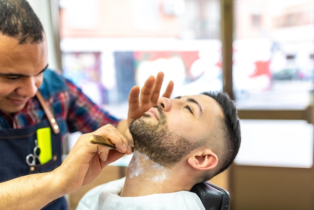 Young man getting a beard shaved