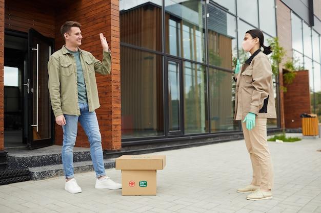 Молодой человек получает посылку с бесконтактной доставкой от доставщика на открытом воздухе