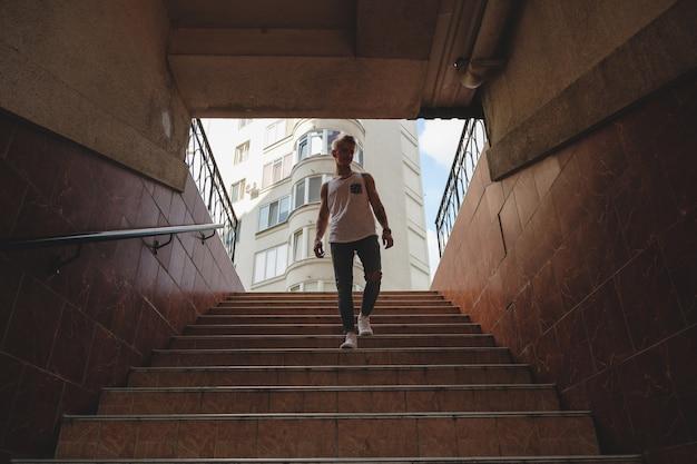 Молодой человек спускается по лестнице в пешеходном метро
