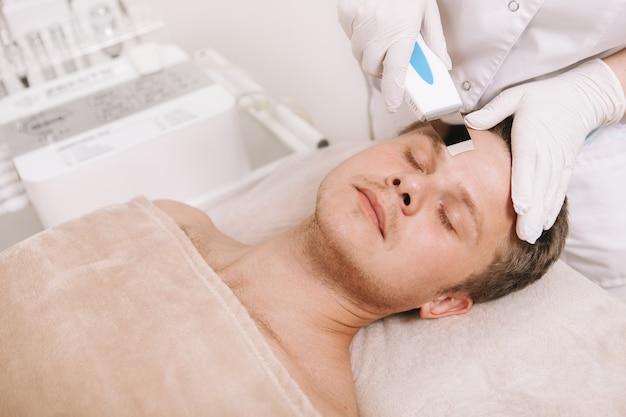 Молодой человек получает уход за кожей лица косметологом