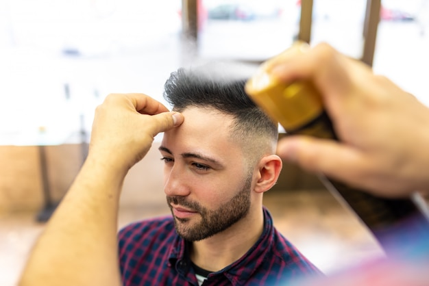 Young man getting a hairstyle in a barbershop.