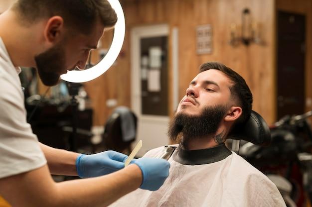 Молодой человек получает свою бороду в парикмахерской