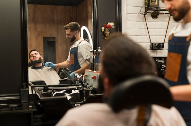 理髪店でひげのスタイルを整える若い男