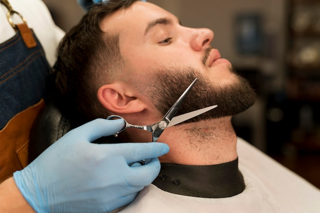 Young man getting his beard styled at the barber