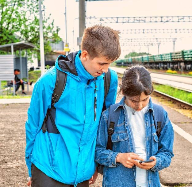 A young man and a girl are considering information in a gadget
