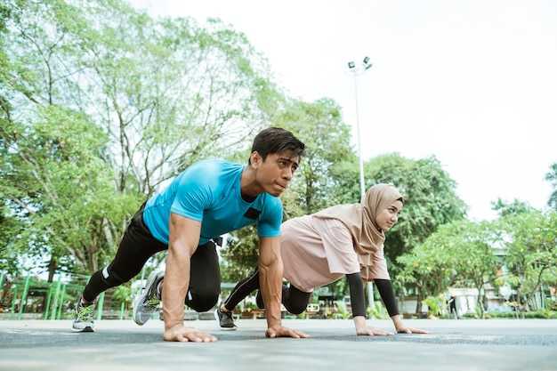 A young man and a girl in a headscarf doing abdominal muscle movements together when outdoor exercise in the park