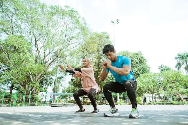 A young man and a girl in a headscarf doing squat movements together when outdoor exercise in the park