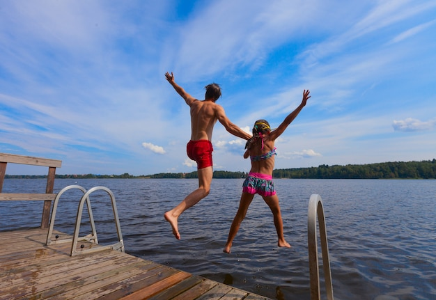 Young man and girl jumping into water
