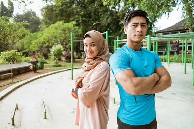 A young man and a girl in a veil stand back to back with crossed hands while exercising in the park