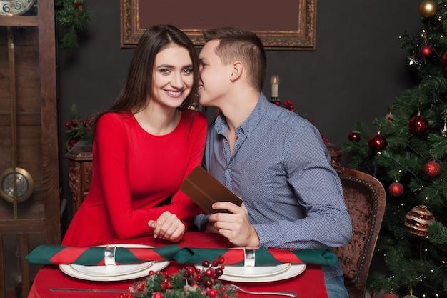 젊은 남자가 아름다운 여자에게 선물을 제공합니다