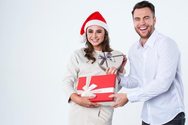 젊은 남자는 흰색 바탕에 여자에 게 선물을 제공합니다. 새해 복 많이 받으세요 그리고 메리 크리스마스.