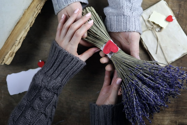 Young man gives a girl a bouquet of lavender flowers on holiday