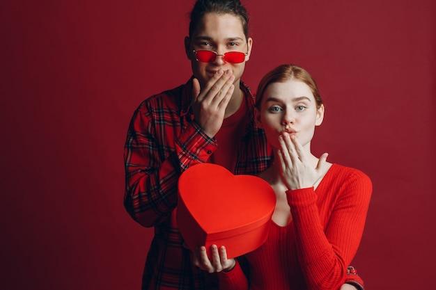 若い男は彼のガールフレンドに赤い背景スタジオでバレンタインデーにハート型の箱を与えます