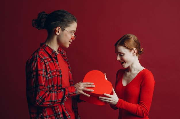 Young man gives his girlfriend a heart-shaped box in valentine's day on red background studio