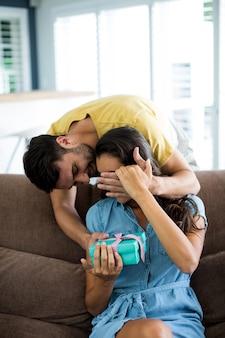 自宅の居間で女性にサプライズギフトを与える若い男