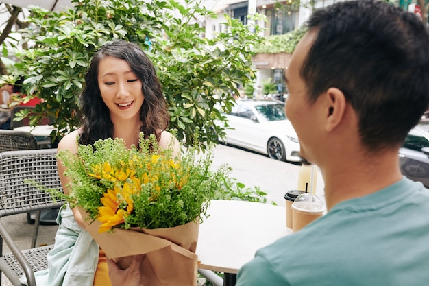Молодой человек дарит букет цветов своей счастливой девушке, когда они встречаются на открытом воздухе