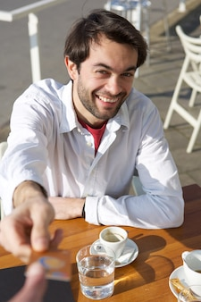 Young man giving credit card for payment at restaurant