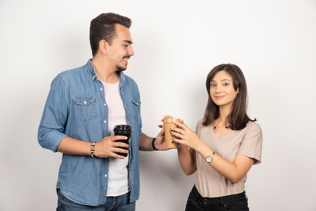 Young man giving a cup of coffee to smiling woman.