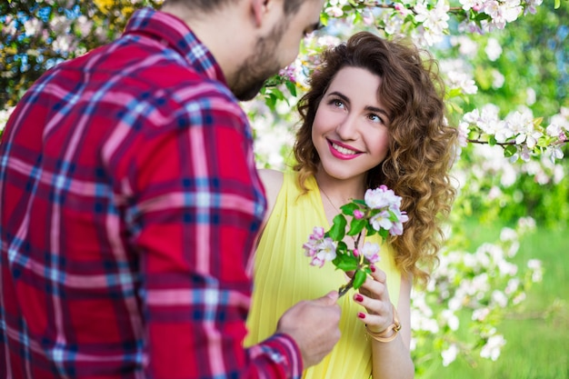 Young man giving flowers to happy girlfriend in summer garden