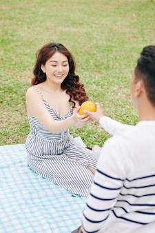 Young man giving fresh orange to his pretty smiling girlfriend when they are sitting on blanket in park