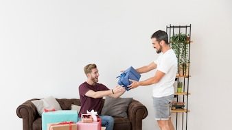 Young man giving gift box to his friend sitting on sofa against white wall