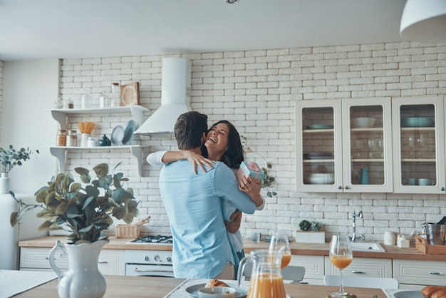 Young man giving a gift to his girlfriend while having breakfast at the domestic kitchen together
