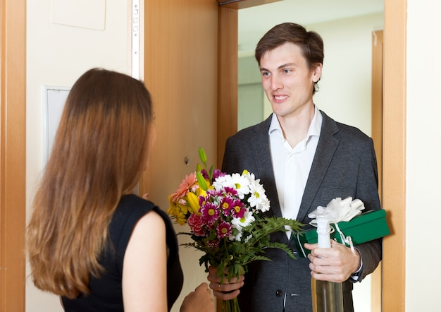 Young man giving gifts to woman
