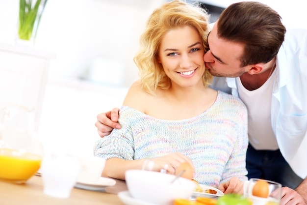 Young man giving a good morning kiss to his wife in the kitchen