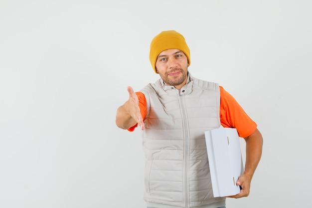 악수, 티셔츠, 재킷, 모자에 골판지 상자를 들고 부드러운 찾고 젊은 남자. 전면보기.