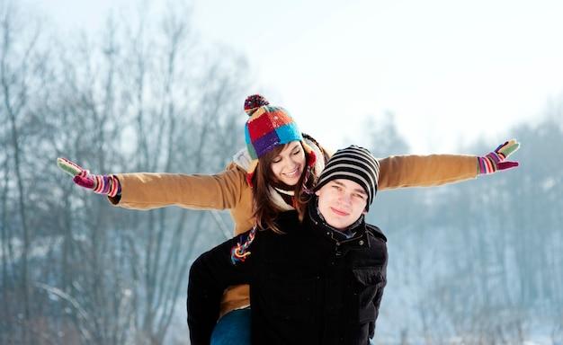彼のガールフレンドにピギーバックライドを与える若い男