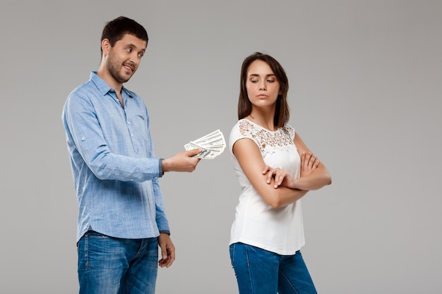 Young man giving money to woman, smiling over grey wall