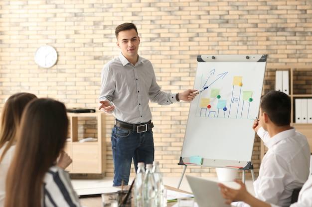 オフィスでのビジネス会議中にプレゼンテーションを行う若い男
