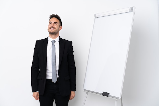 Young man giving a presentation on white board and looking up while smiling