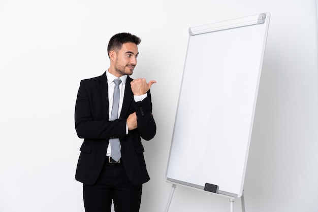 Young man giving a presentation on white board and pointing to the side