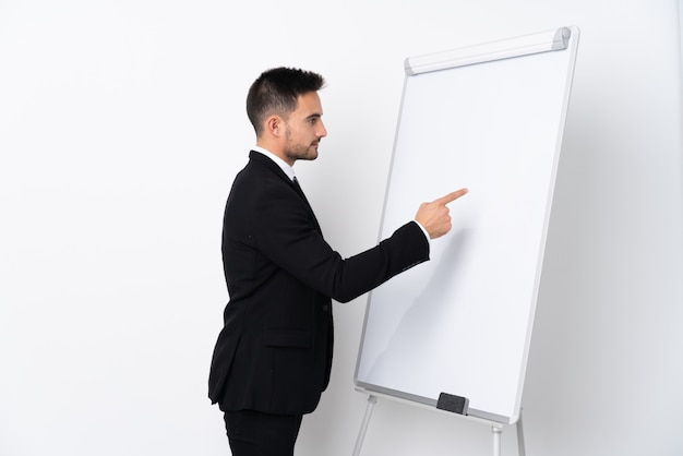 Young man giving a presentation on white board and writing in it