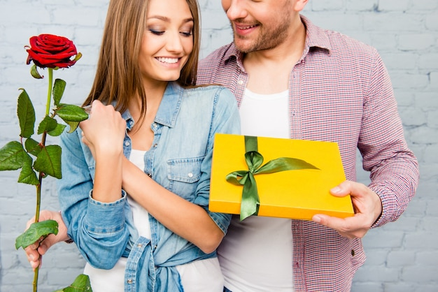 Young man giving red rose and present to his girlfriend