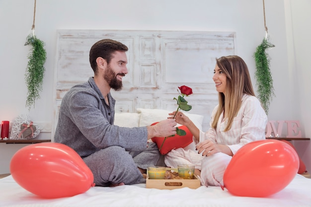 Young man giving red rose to woman on bed