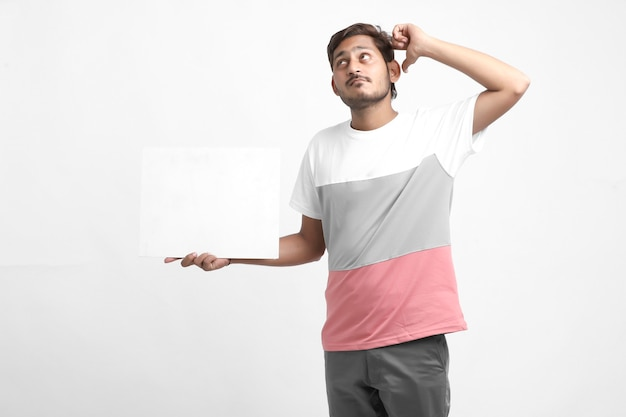 Young man giving thinking expression and holding blank poster