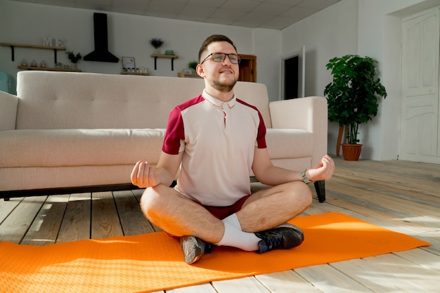 Young man in glasses doing yoga on mat at home