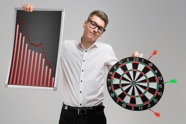 Young man in glasses holding a board with falling statistics and darts isolated on white background