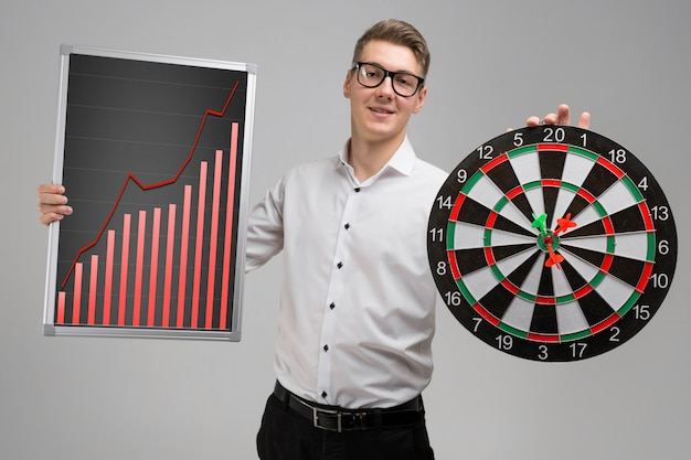 Young man in glasses holding a board with increasing statistics and darts on white