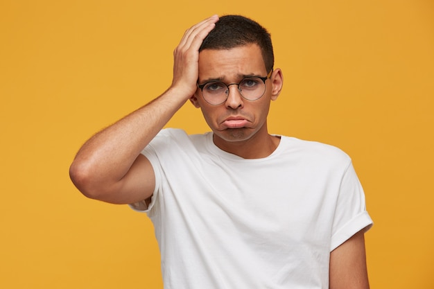 Young man in glasses looks sad, upset, frustrated and displeased