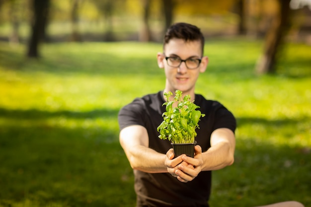 Young man in glasses resting in a park and stretches hands with pot of basil on green background. health lifestyle