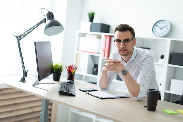 A young man in glasses stands near a table in the office.