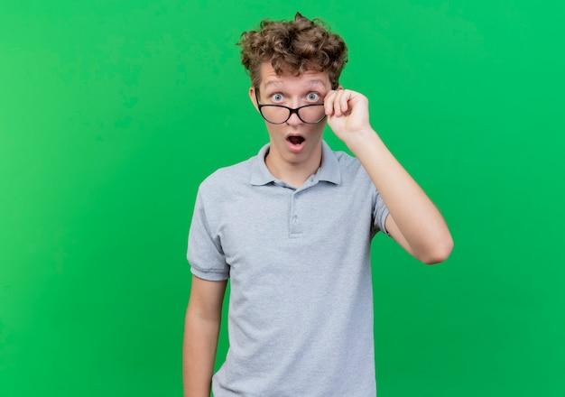 Giovane uomo con gli occhiali che indossa una polo grigia con gli occhiali fuori sorpreso e stupito in piedi sopra il muro verde