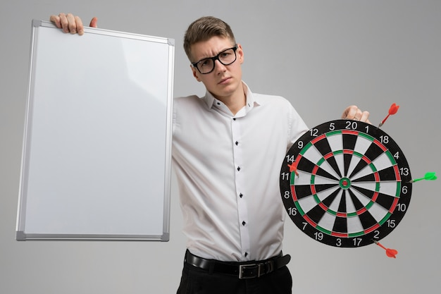 Young man in glasses with target with dart not in center and empty plate in his hands on white