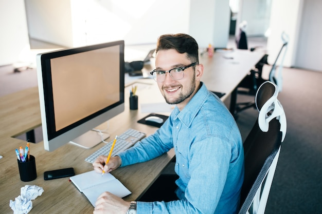 Young man in glassess is working at his workplace in office. he wears blue shirt.  he is writing in notebook and smiling to the camera.